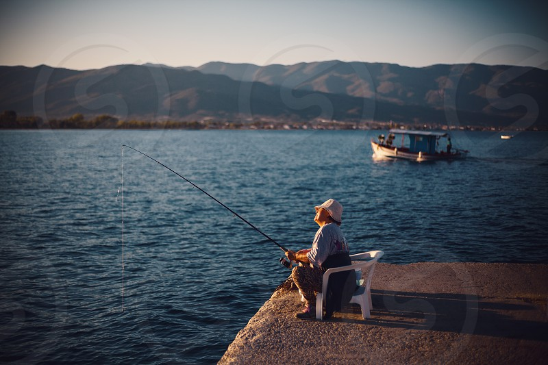 Stavros Greece - September 06 2017: Older woman fishing with stick on sea dock.  photo