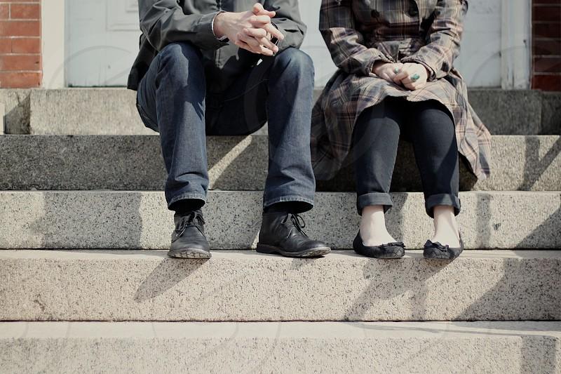 man in blue denim pants sitting next tot lady in black pants photo