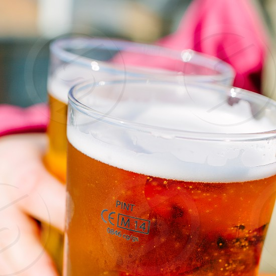 Two pints of beer being carried outdoors photo