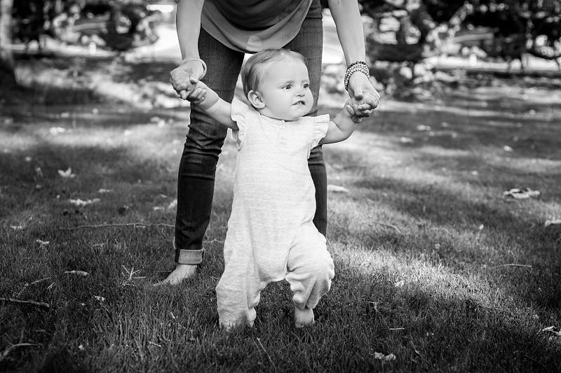 woman holding baby walking photo