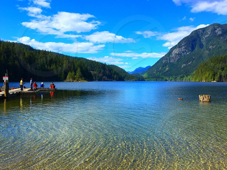 Mountains lake dock people fishing calm serene blue water outdoors British Columbia reservoir bunt Em lake Canada natural recreation summer glacial lake scenery beauty relaxation early morning photo
