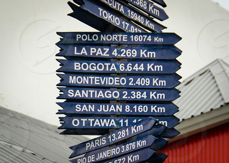 Sign post pointing to more than a dozen distant cities around the world from Ushuaia Tierra del Fuego Argentina the southernmost city in the world. photo