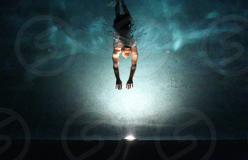 Male swimming in water at night. photo