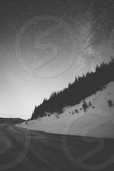 black and white monochrome road mountain snow snowy forest stars milky way night winter cold freezing frozen photo
