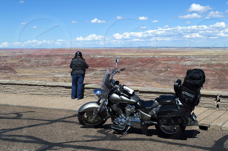 Lady biker with motorcycle loaded down with luggage from travel  pausing to take a admire the beauty of Arizona's Painted Desert. photo