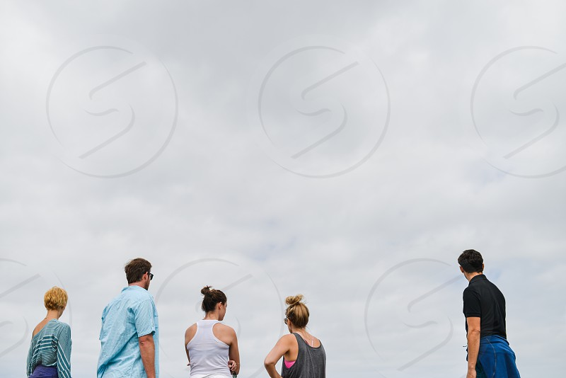 man in black polo shirt standing near 3 women and man in blue button up shirt wearing sunglasses under white sunny cloudy sky photo