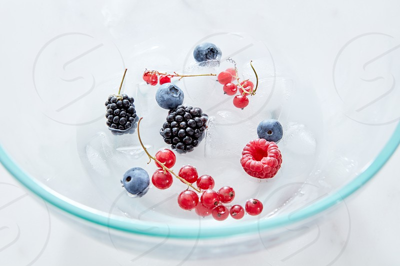 Close-up glass bowl with different fresh berries and ice cubes on a gray marble background with space for text. Top view photo