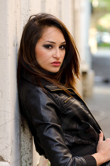 Woman young woman long hair brown hair outdoors natural light leather jacket standing Hispanic beautiful edgy leaning attitude  photo