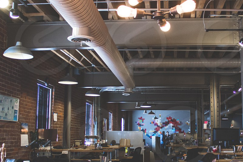 interior of red brick restaurant with exposed piping ceiling photo