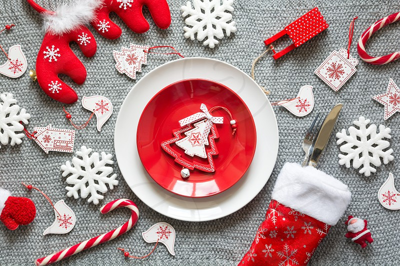 Christmas table setting with Christmas decorations on grey knitted background. Top view. Flat lay photo