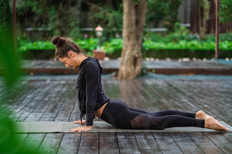 Concentrated girl sitting in lotus pose and meditating or praying. Young woman practicing yoga alone on wooden deck in tropical island photo