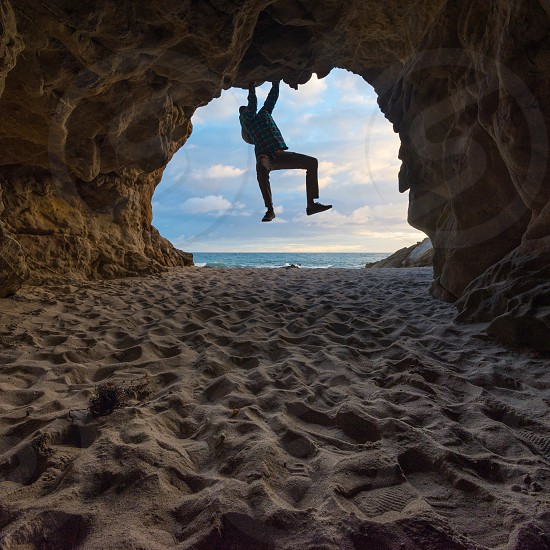 man hanging at the entrance of a cave photo