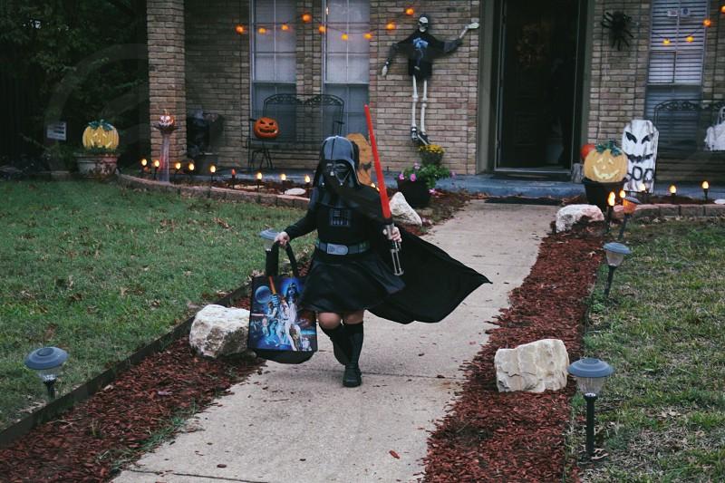 children wearing darth vader costume holding red light saber and bag photo