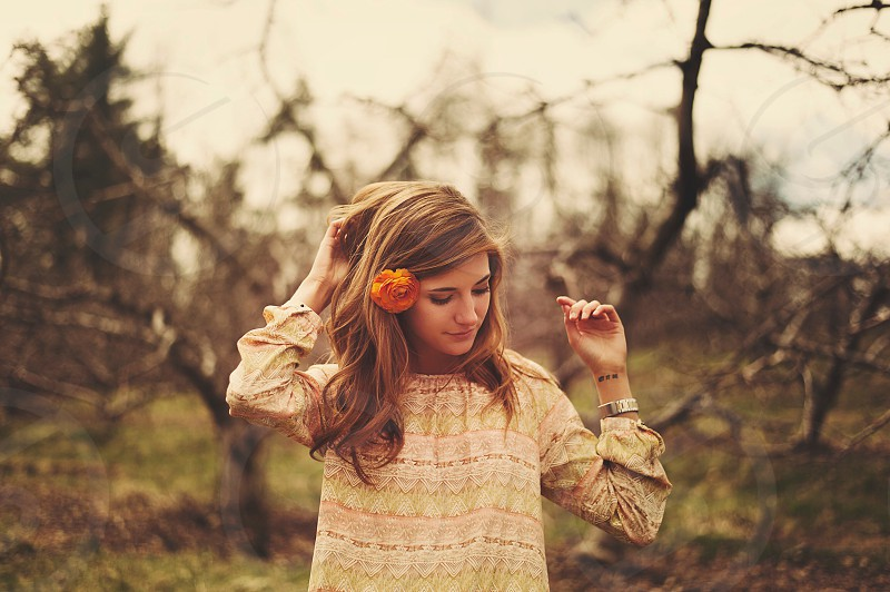 woman in forest with flower in long blonde hair wearing vintage taupe blouse photo