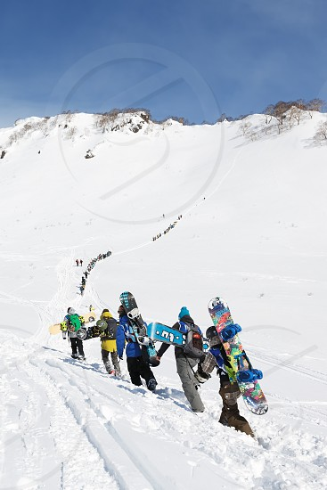 KAMCHATKA PENINSULA RUSSIAN FEDERATION - MARCH 9 2014: Group of snowboarders climbing the mountain for freeride. Competition Kamchatka Freeride Open Cup. Kamchatka Region Russian Far East Eurasia. photo