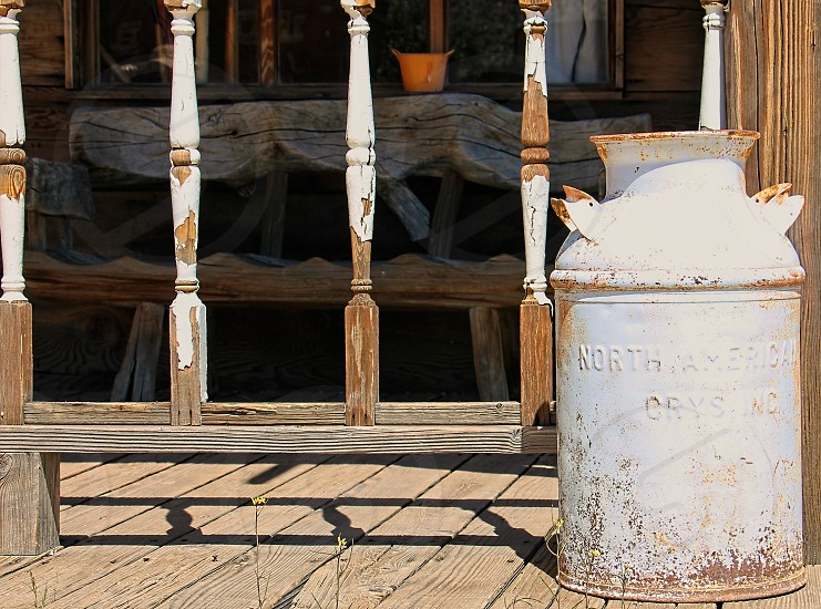 White milk can on a wooden front porch photo