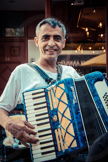 man in white t shirt playing a blue accordion photo