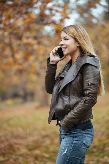 Young woman using smartphone in the park in autumn photo