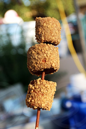 S'more on a stick -- marshmallows covered in chocolate and graham cracker crumbs -- fair or festival photo