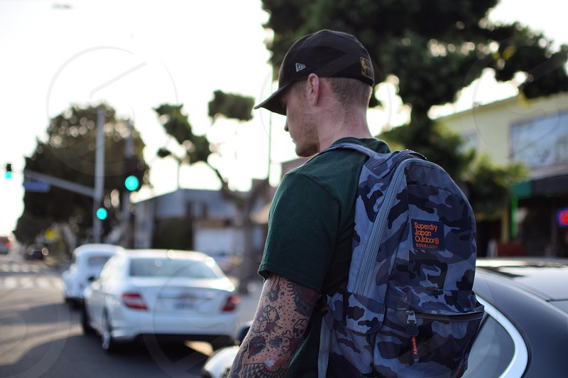man in green shirt wearing camouflage backpack and black cap photo