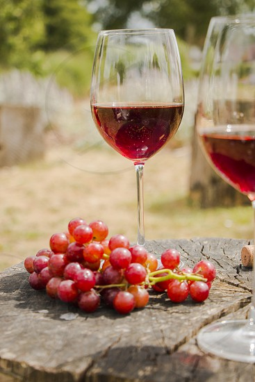 Glasses with red wine and red grapes in outdoor space photo
