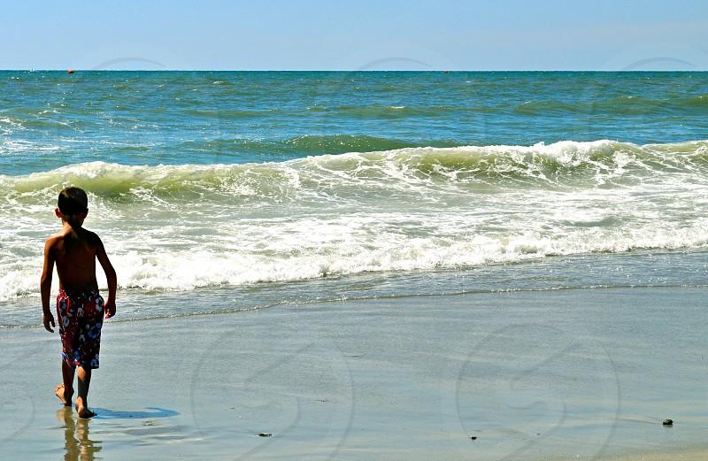 Boy walks on the beach - Myrtle Beach South Carolina - USA photo