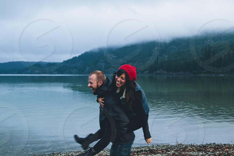 man giving piggy back ride to woman photo