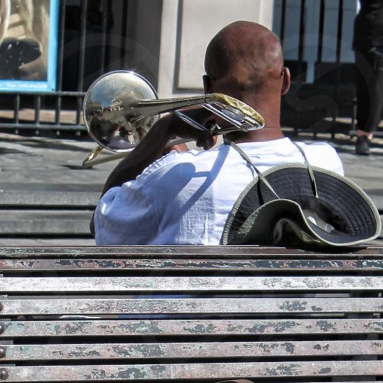 Seen from behind a man plays his trumpet sitting on a park bench. photo