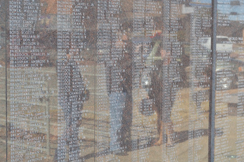 Reflection of people standing in front of a veteran's memorial solemnly remembering the fallen soldiers whose names are engraved on the wall. photo