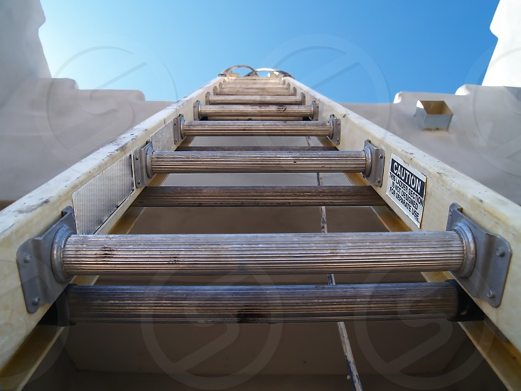 A long aluminum ladder leading up to the roof of a home. photo