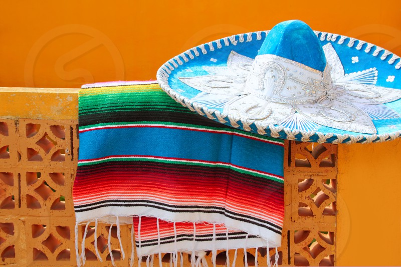 charro mariachi blue mexican hat serape poncho over orange tiles wall photo