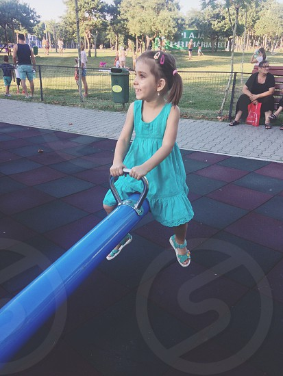 girl wearing turquoise sleeveless dress playing see saw during daytime photo