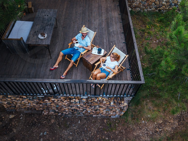 Young couple drinking coffee on terrace aerial view photo