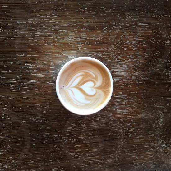 white and brown coffee details in cup on brown wooden surface photo