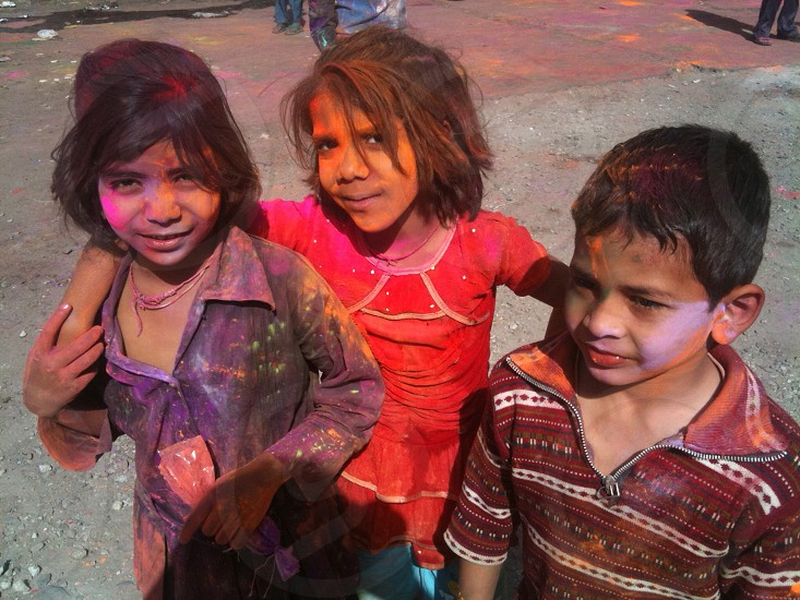 three children with assorted paints on their faces taking photo together photo