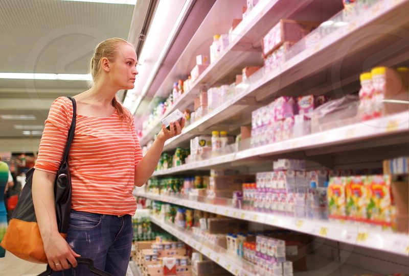 Young caucasian woman is holding a packaging baby milk in the department of baby food in the supermarket photo