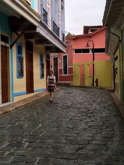 woman walking on street beside house photo