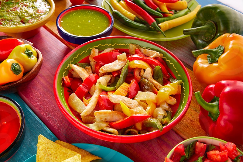 Chicken fajitas with mexican food guacamole pico de gallo chili peppers sauce and nachos photo