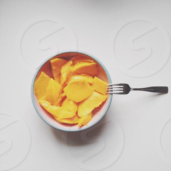 yellow sliced mango in bowl photo