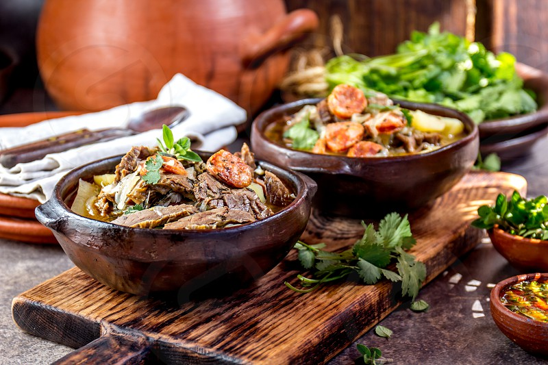 Chilean Ajiaco. Latin American food. Ajiaco - traditional chilean soup with grilled meat onion and potato served in clay plates. photo