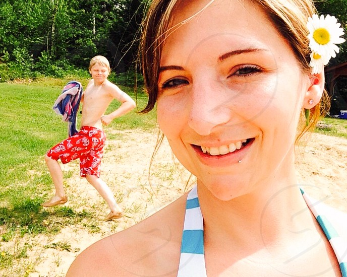 boy wearing res shorts behind smiling woman wearing blue and white halter top during daytime photo