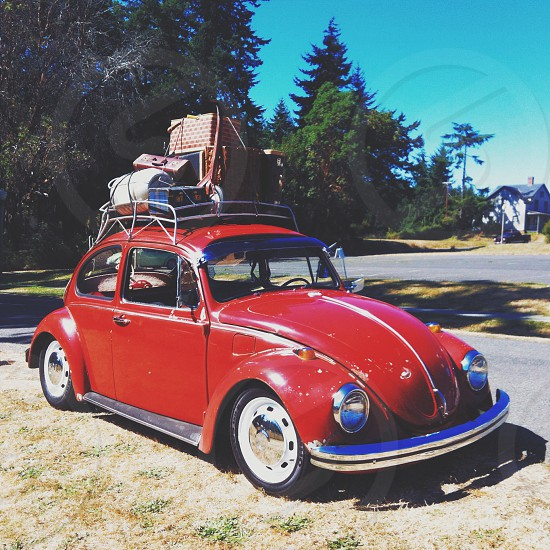 red volkswagen beetle with bag on roof photo