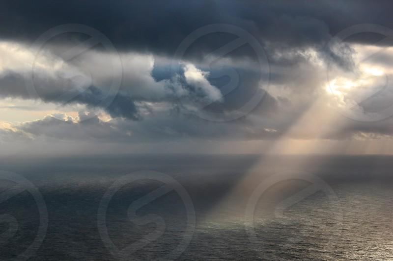 sun ray through the cloudy sky to the ocean photo