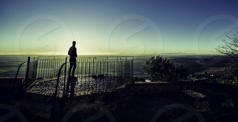 Silhouette of young boy watching sunrise photo
