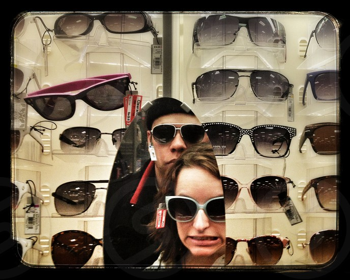man and woman trying out sunglasses photo