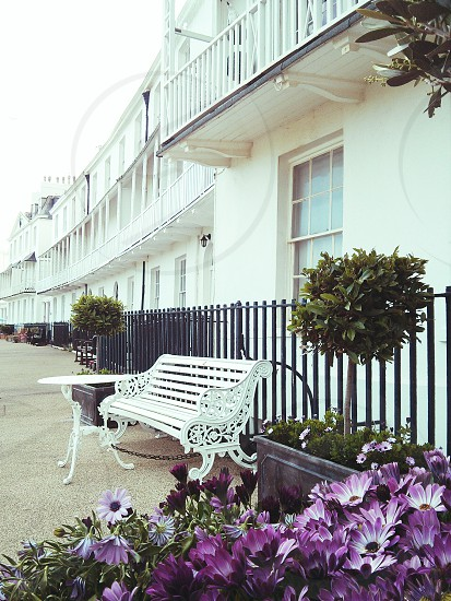 Outdoor furniture in front of the white 18th century seaside homes of Fortfield Terrace Sidmouth Devon UK. These houses were once regularly graced by European royalty. photo
