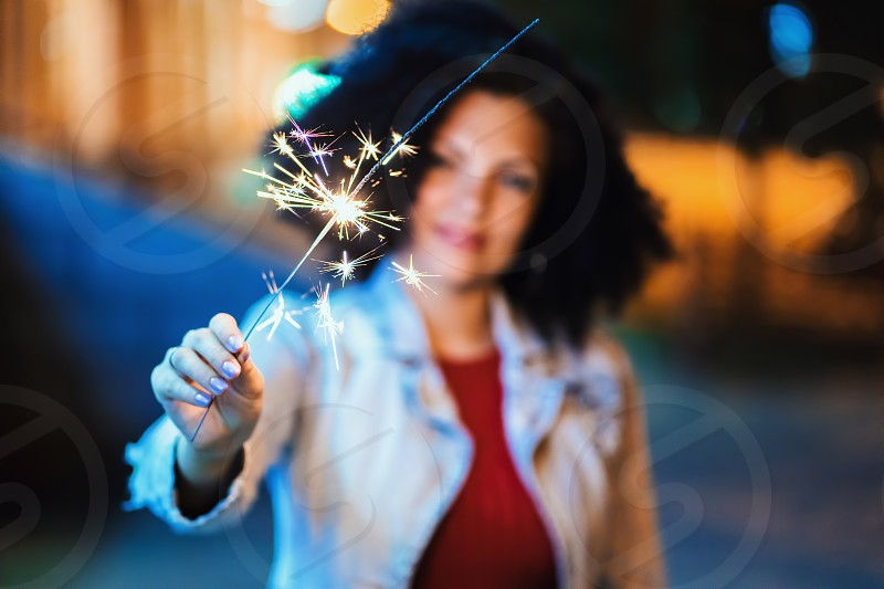 Young beautiful woman with very curly afro hair dancing with bengal fire at night illuminated street. Unusual trendy girl with sparklers. Holiday concept. photo