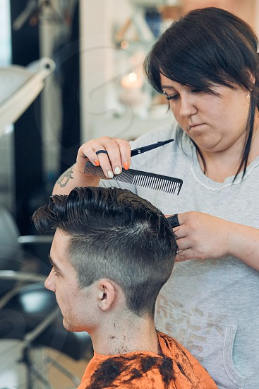 Hairdresser haircutting styling young man's hair in barbershop. Young woman working as a hairdresser in hair salon. Real people authentic situations photo