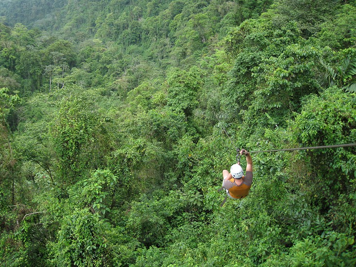 Wide angle view of a man ziplining through the rainforest in the Arenal Volcano region of Costa Rica photo
