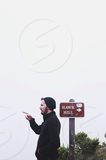 man pointing away from hawk hill sign photo